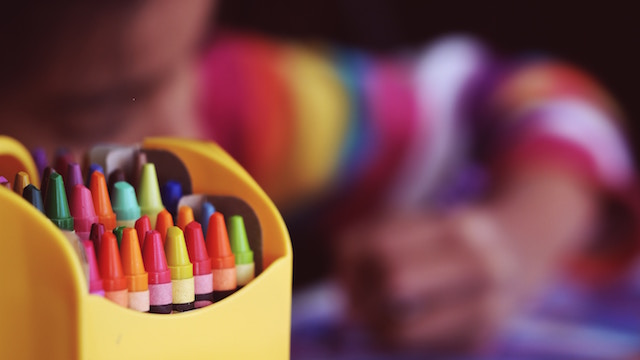 a child coloring with crayons