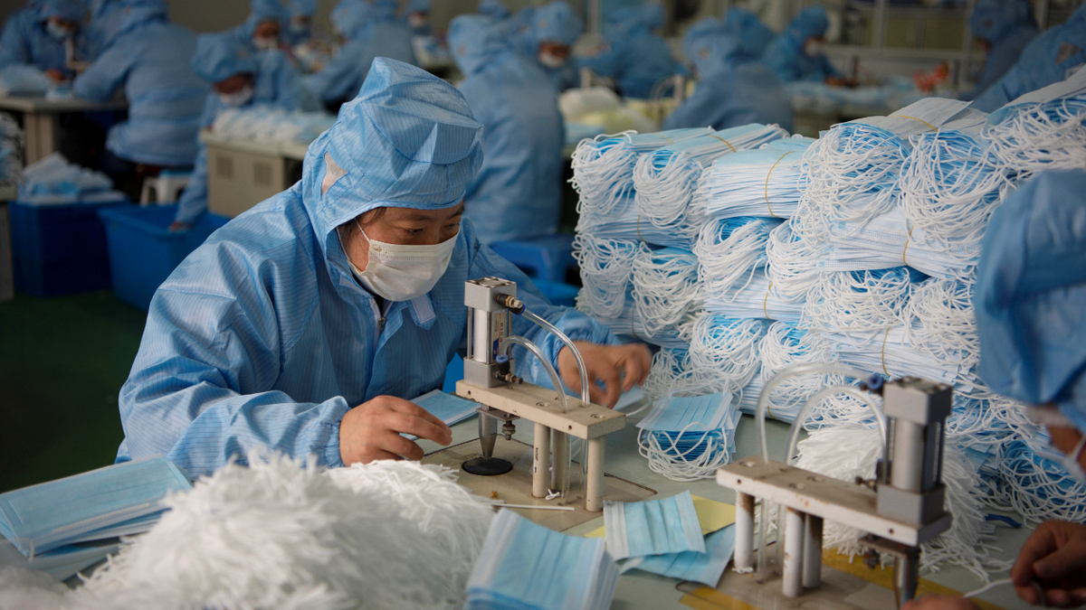 Factory employees in China work on a production line for surgical masks