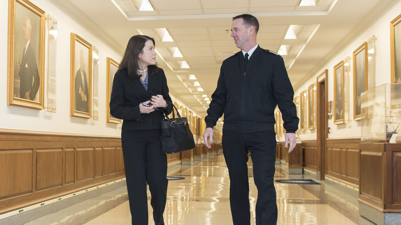 Jennifer Lerner and John Richardson, Chief of Naval Operations, walk down a long corridor during one of her visits to the Pentagon.