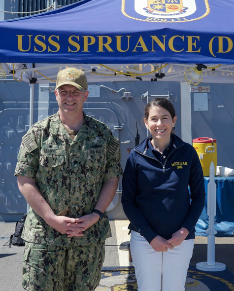 Jennifer Lerner stands with Commander Josh Menzel on a dock in front of the Arley Burke-class destroyer USS Spruance, in port in San Diego.