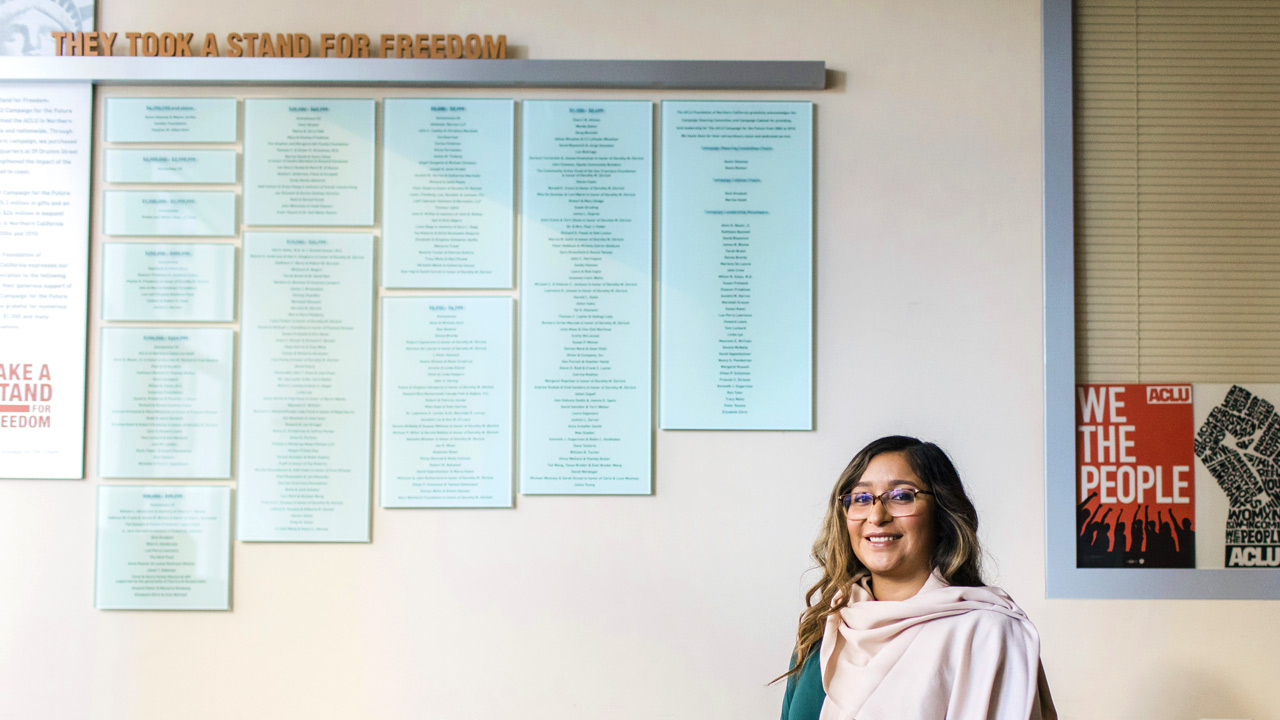 Christina Fletes MC/MPA 2016 stands in front of a plaque of names in the lobby of the ACLU office in Northern California.