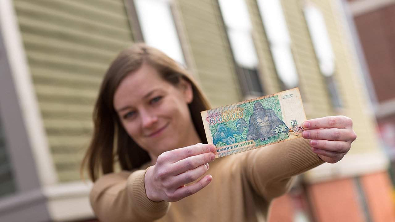 Political economy and government doctoral alumna Sara Lowes displays currency from Zaire