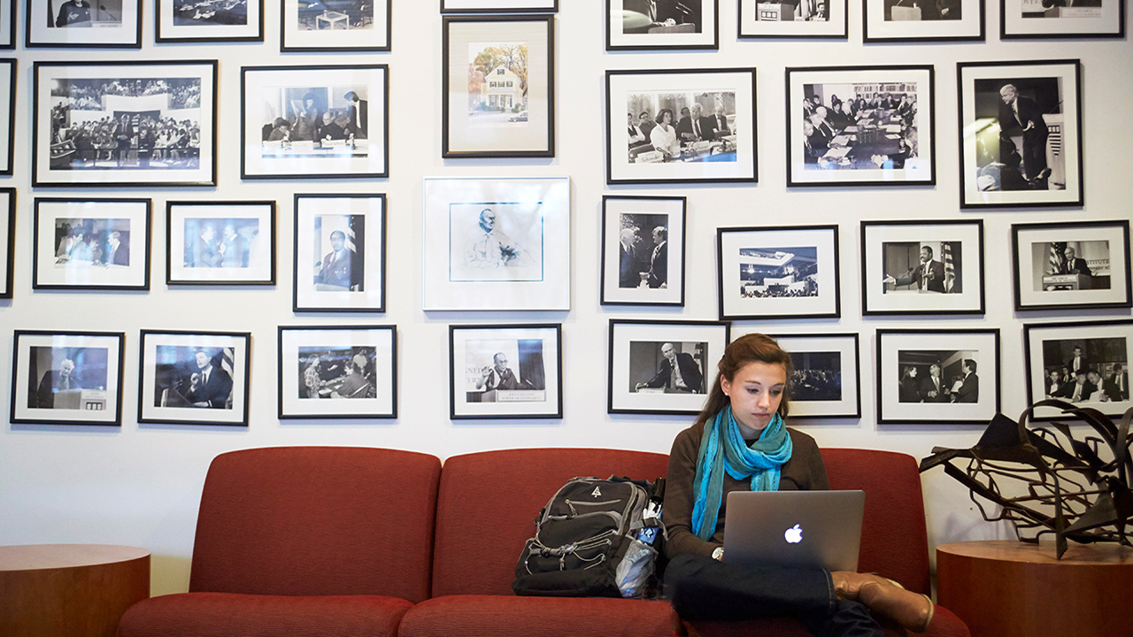 A student sits in front of historical photographs at Harvard Kennedy School
