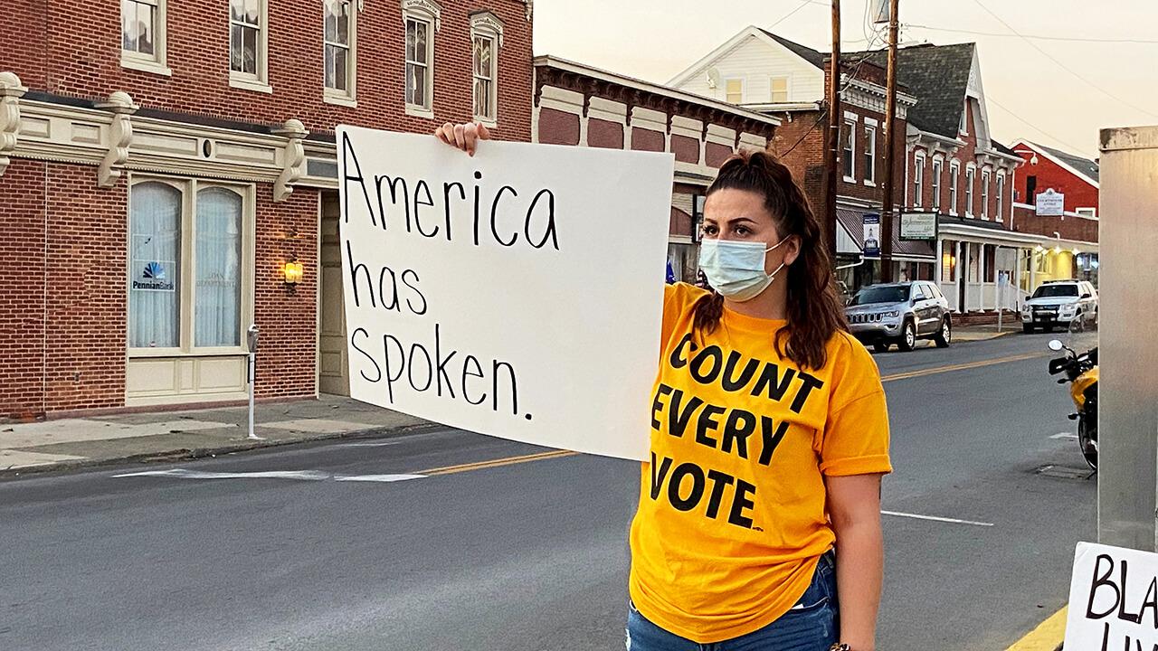 Demonstrator holds sign.