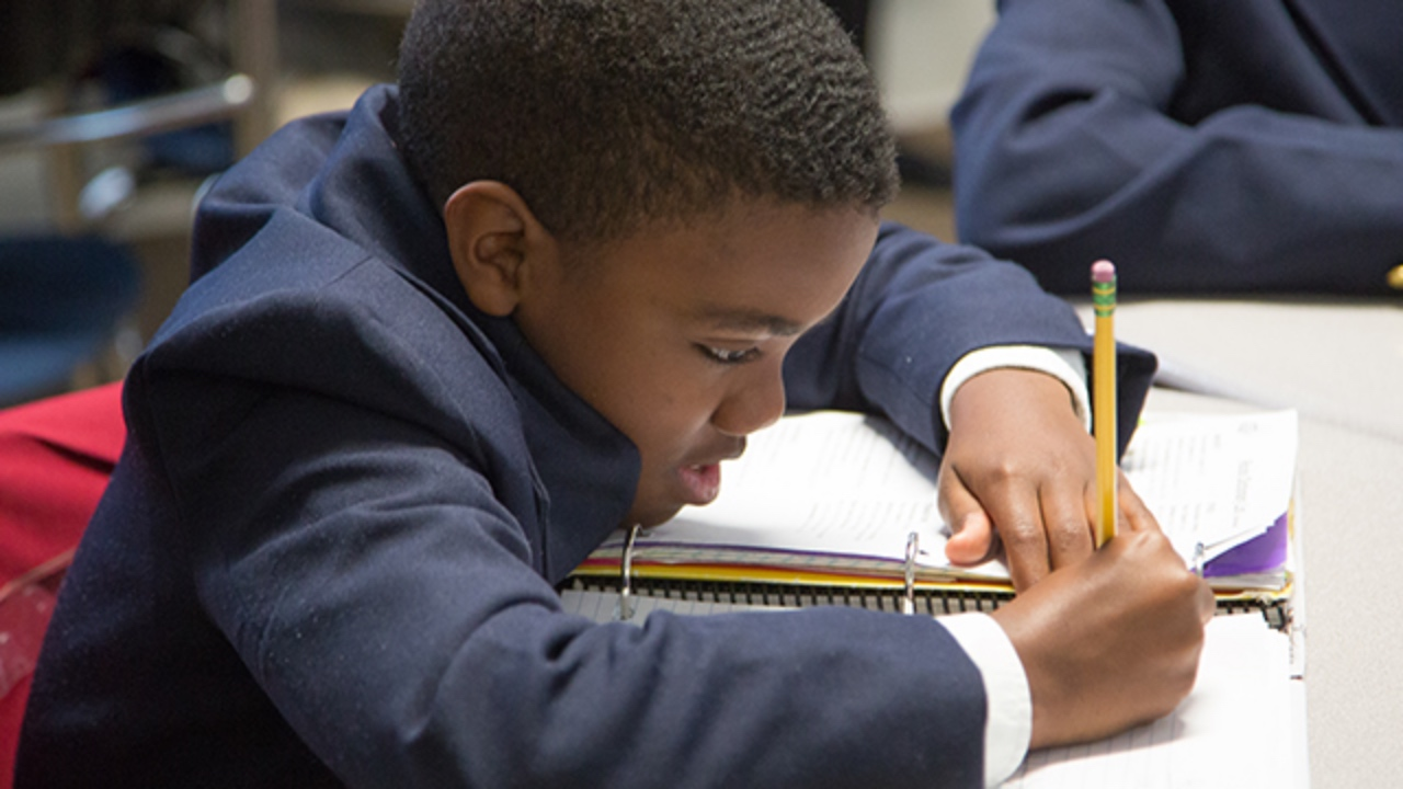 Young charter school student studies at his desk.